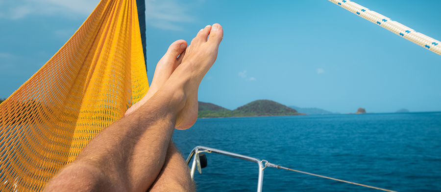 Man relaxing in the hammock set on the sail boat anchored in the sea
